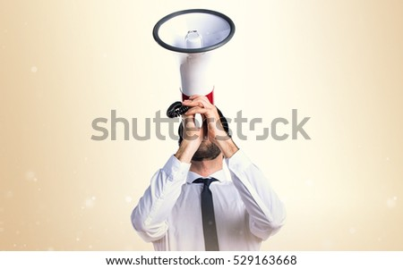 Handsome telemarketer man shouting by megaphone on ocher background