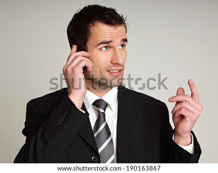 Handsome thinking man in suit with talks at mobile phone