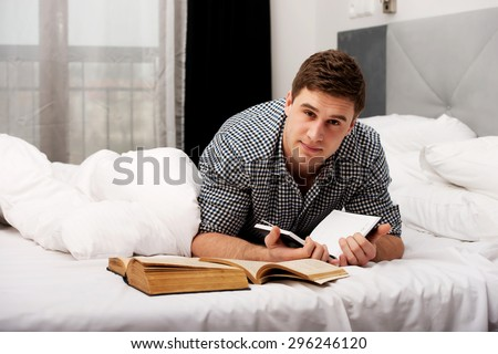 Handsome thoughtful man with a book in his bed. - stock photo