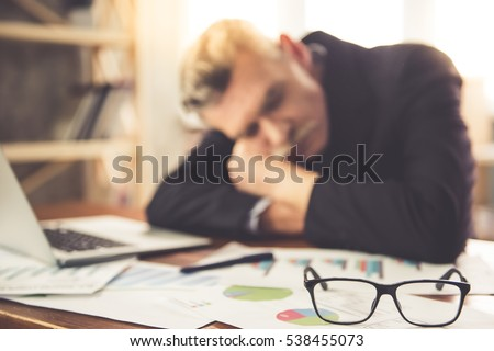 Handsome tired mature businessman in classic clothes is napping on the table while working in office