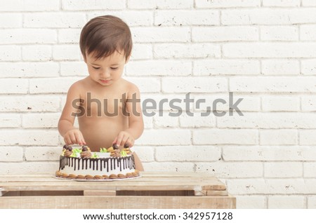 handsome toddler playing with his cake on white walls background - stock photo
