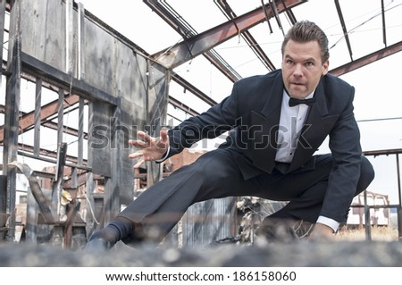 Handsome tough Caucasian man in black tuxedo poses in action stunt scene in destroyed warehouse - stock photo