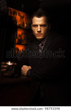 Handsome Tough Young Man With A Serious Look Standing In A Dark Bar With A Drink In A Bar Room Brawl And Fight Club Conceptual - stock photo