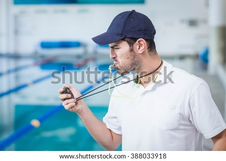 Handsome trainer blowing whistle and looking at stopwatch at the pool - stock photo