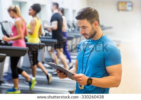 Handsome trainer looking at clipboard at the gym - stock photo