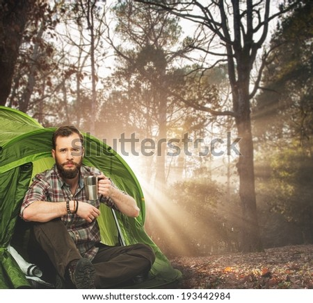 Handsome traveler near tent with coffee cup in autumnal forest - stock photo