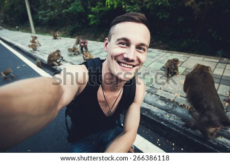 Handsome traveling man takes selfie photo with wild monkeys in tropical jungle forest in Phuket, Thailand, Asia - stock photo