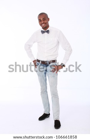 Handsome,Trendy and fashionable African American business man wearing jeans,long white shirt and a silver bow tie with a huge smile showing teeth on his face and holding his hands on his hips. - stock photo