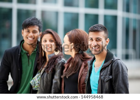Handsome trendy young Asian man standing outdoors in the town with his friends smiling at the camera - stock photo