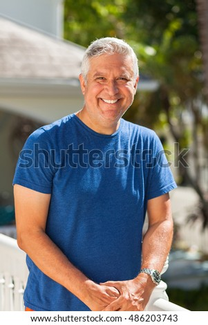 Handsome unshaven middle age man outdoor portrait in a home setting.