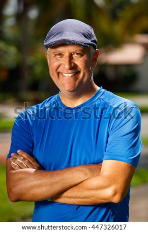 Handsome unshaven middle age man outdoor portrait wearing a stylish hat.