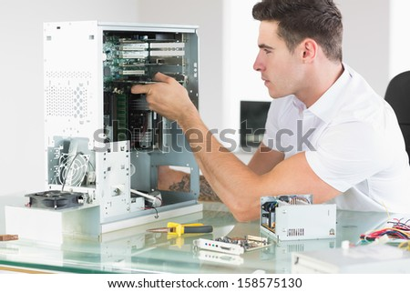 Handsome unsmiling computer engineer working at open computer in bright office - stock photo