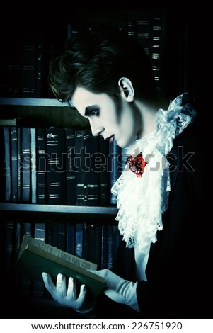 Handsome vampire nobleman studying ancient books in the library. Halloween. Dracula costume. - stock photo