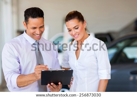handsome vehicle dealership principal and saleswoman looking at clipboard - stock photo