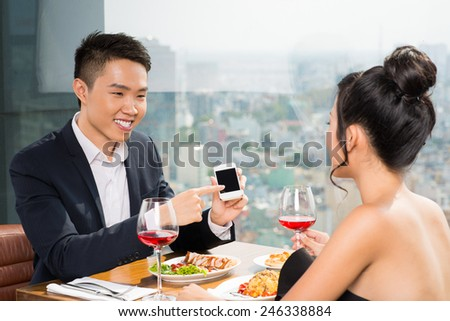 Handsome Vietnamese man showing his girlfriend a smartphone while they are dining in the restaurant - stock photo