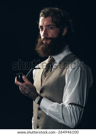 Handsome vintage man with a bushy beard wearing a stylish and armbands standing looking at the camera holding a pipe in his tattooed hand - stock photo