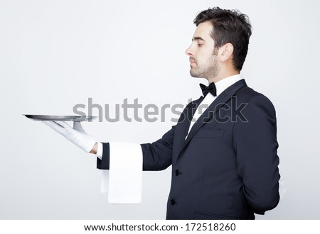 Handsome waiter holding an empty silver tray over gray background
