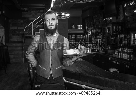 Handsome waiter in a restaurant with tray. Black and white edit. - stock photo