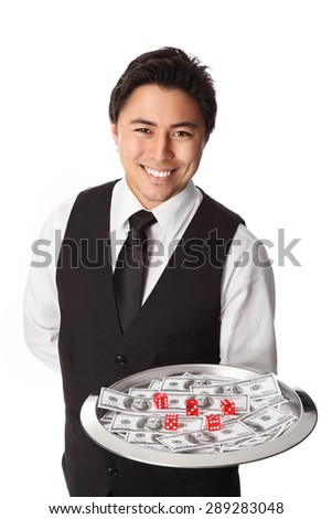 Handsome waiter in a white shirt and black vest serving cash on a tray. With 5 red dices. Standing with a white background. - stock photo