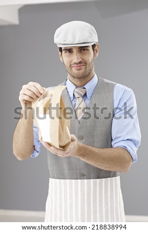Handsome waiter in takeaway restaurant handing sandwich wrapped in paper bag, smiling, looking at camera. - stock photo