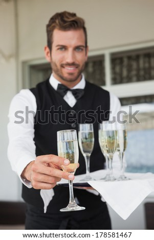 Handsome waiter offering flute of champagne in the patio of restaurant