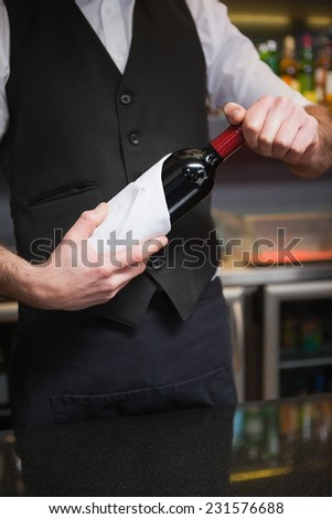 Handsome waiter opening a bottle of red wine in a bar
