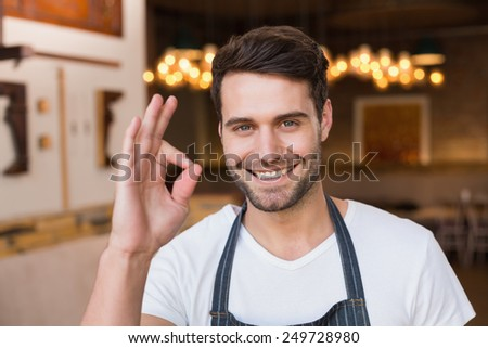 Handsome waiter smiling at camera at the cafe - stock photo