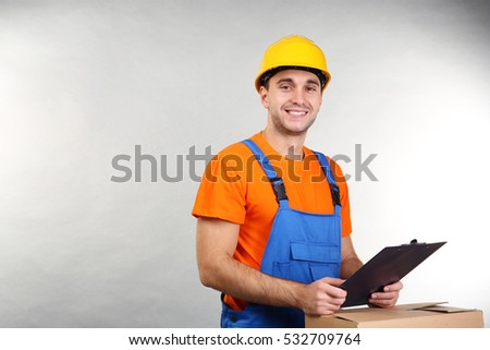 Handsome warehouse worker with clipboard and carton box on light background