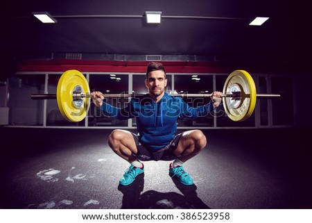 Handsome weightlifter at gym doing squats. - stock photo