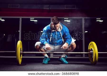 Handsome weightlifter preparing for training. Shallow depth of field, selective focus on hands and dust. - stock photo