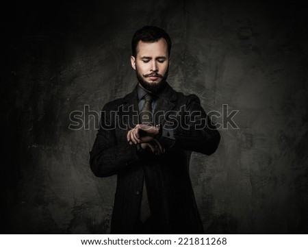Handsome well-dressed man in jacket looking at wrist watch  - stock photo