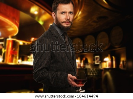 Handsome well-dressed man in jacket with glass of beverage in restaurant interior  - stock photo
