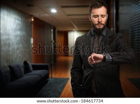 Handsome well-dressed man with beard looking at his wrist watch in a hallway - stock photo