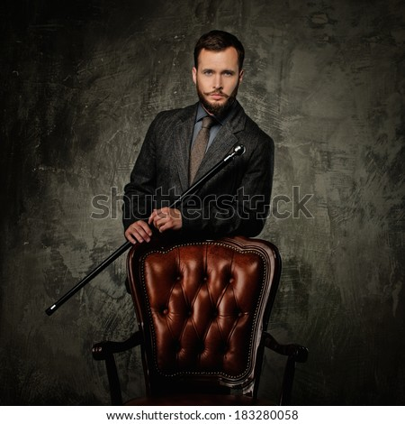 Handsome well-dressed man with stick standing near leather chair  - stock photo
