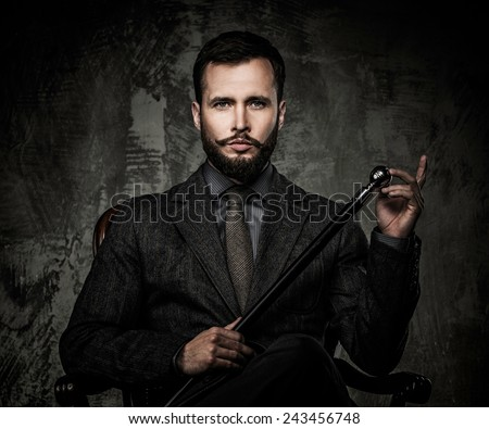 Handsome well-dressed man with walking stick sitting in leather chair  - stock photo