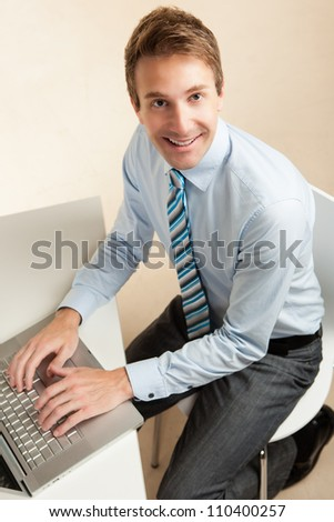 Handsome white professional at work wearing a blue shirt and tie.