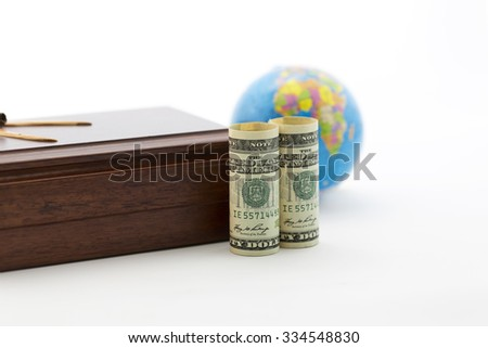 Handsome wood box and American currency in foreground with soft focus on blue globe in background.  Business travel, security, and investment reflected.