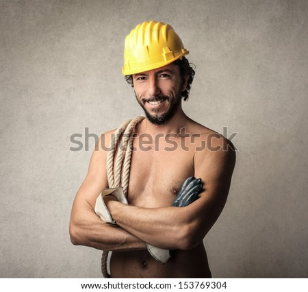 handsome worker with yellow helmet and rope on his shoulder