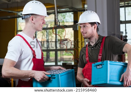 Handsome workers talking in a factory, horizontal - stock photo