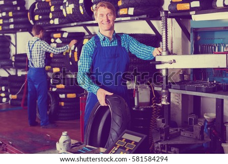 Handsome working man standing with new tires for motorbike in hands in workshop