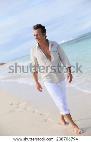 Handsome 40-year-old man walking on beach - stock photo