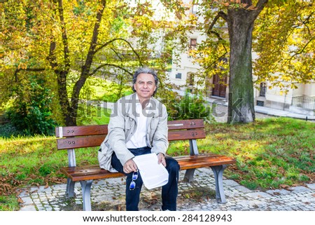 Handsome 50 years old man with salt pepper hair and green eyes dressed with grey gabardine, linen white shirt and blue pants is reading documents in a park in Prague
