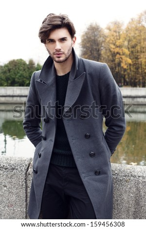 Handsome yong man in autumn coat. Outdoor fashion male portrait - stock photo