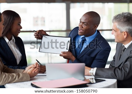handsome young african american businessman presenting figures at a meeting with team