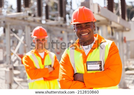 handsome young african american electrical engineer with arms crossed in substation - stock photo