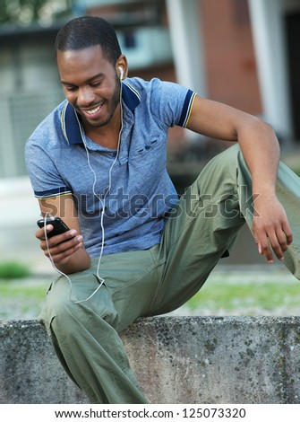 Handsome young African American man smiling and listening to music on his earphones - stock photo