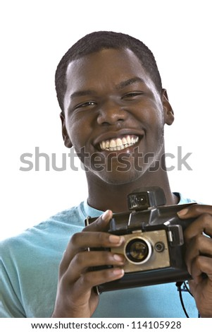 Handsome young African-American smiling while holding a vintage camera in front of white background - stock photo
