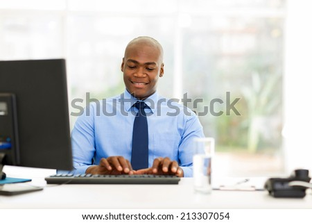 handsome young african businessman working in office - stock photo