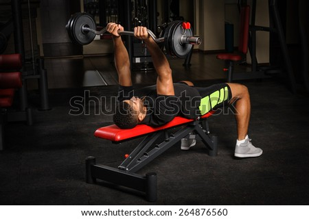 handsome young african descent mixed race man doing bench french press workout with barbell in gym - stock photo