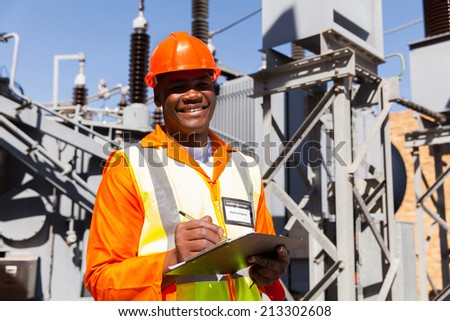 handsome young african electrical engineer holding clipboard in power station - stock photo